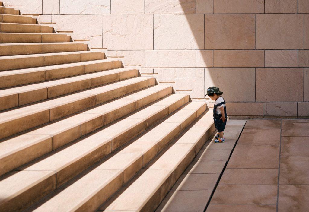 child contemplates a staircase